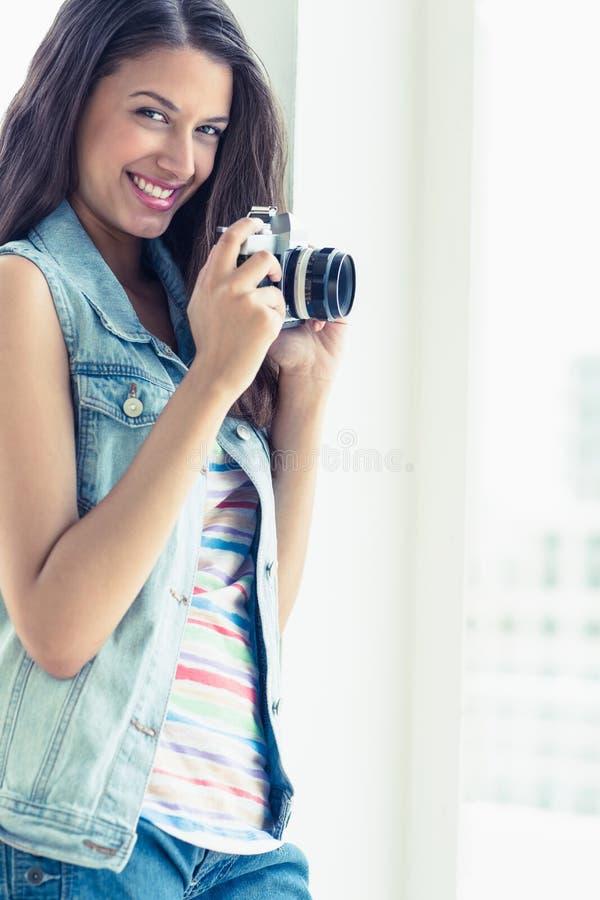 Modieuze jonge vrouw die een foto nemen die bij camera glimlachen stock afbeeldingen