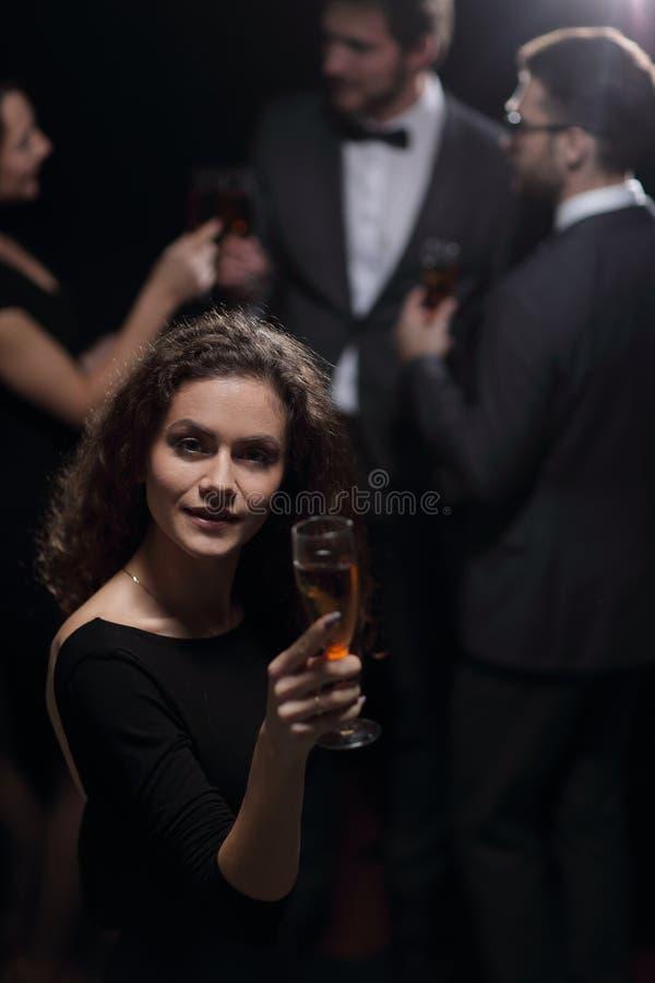 Modieuze jonge vrouw die een glas champagne opheffen royalty-vrije stock afbeeldingen