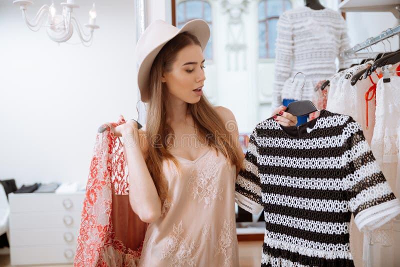 Modieuze jonge vrouw die en kleding in kledingsopslag bevinden zich kiezen stock afbeelding