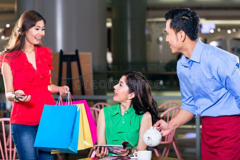 Modieuze jonge vrouw die gelukkig voor het ontmoeten van een vriend in een koffiewinkel kijken royalty-vrije stock afbeelding