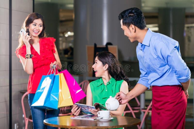 Modieuze jonge vrouw die gelukkig voor het ontmoeten van een vriend in een koffiewinkel kijken royalty-vrije stock foto