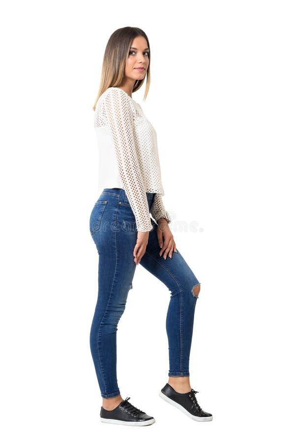 Modieuze jonge in vrouw die in jeans en gevlecht wit overhemd camera bekijken stock afbeeldingen