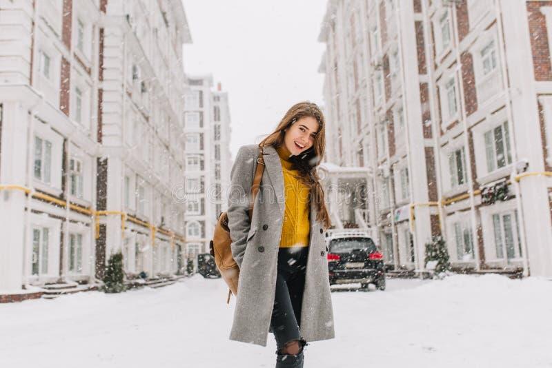 Modieuze jonge vrouw die in laag met rugzak op straat in grote stad in sneeuwende tijd lopen Vrolijke stemming, sneeuwval royalty-vrije stock foto