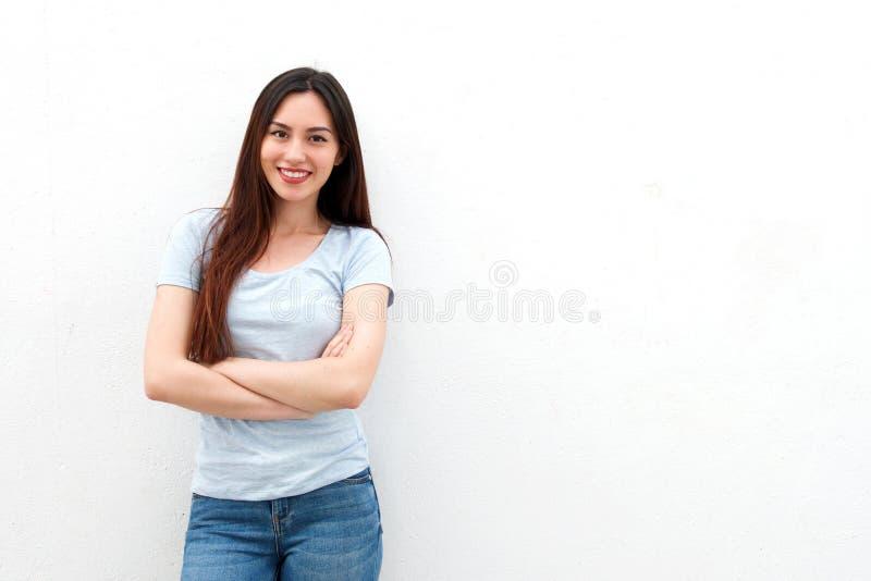 Modieuze jonge vrouw die met gekruiste wapens glimlachen stock fotografie
