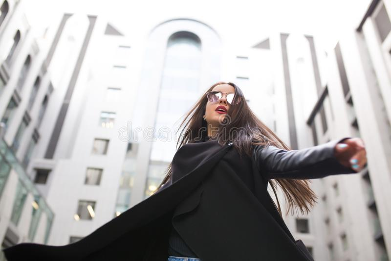 Modieuze jonge vrouw die met lang haar in glazen bij CIT lopen stock afbeelding