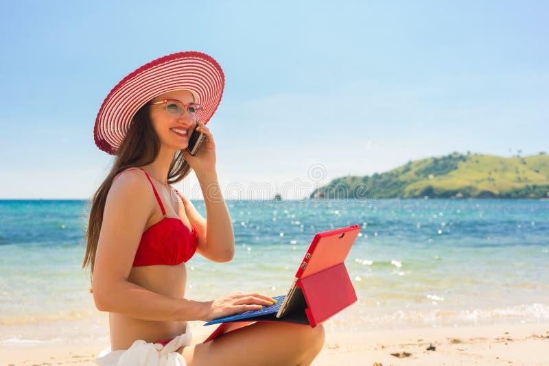 Modieuze jonge vrouw die op mobiele telefoon bij het strand spreken stock afbeelding