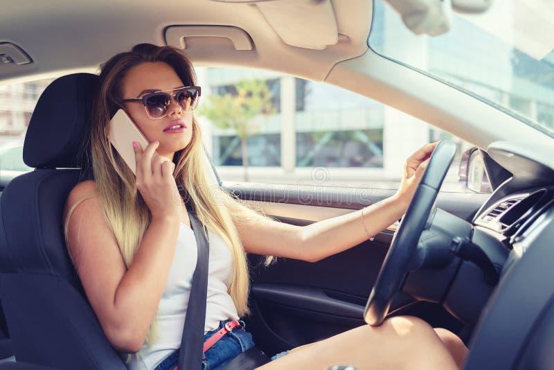 Modieuze jonge vrouw die op mobiele telefoon spreken terwijl het drijven van nieuwe auto na het krijgen van rijbewijs stock foto