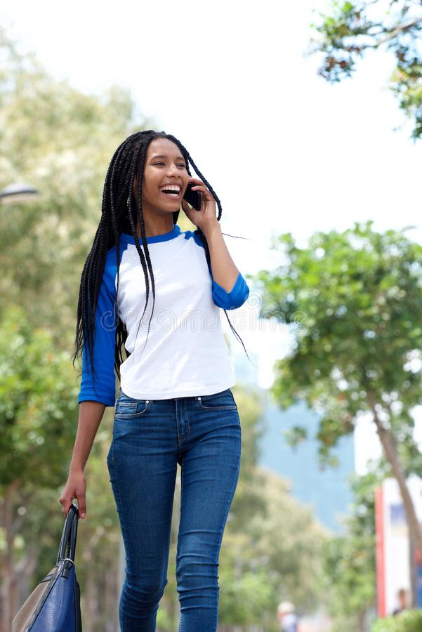 Modieuze jonge vrouw die in openlucht in de stad lopen en op mobiele telefoon spreken stock foto