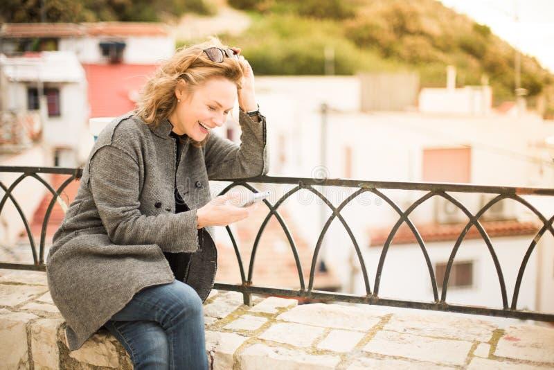 Modieuze jonge vrouw in een grijze laag buiten huis lachen die in haar telefoon kijken stock afbeelding
