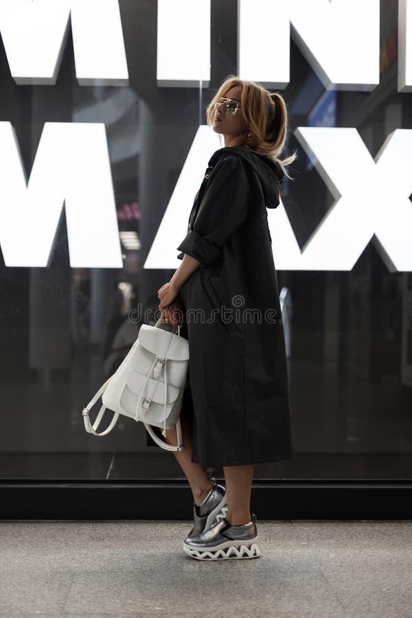Modieuze jonge vrouw in een lang modieus jasje in glazen met een kapsel in zilveren schoenen met leerrugzak het stellen royalty-vrije stock foto