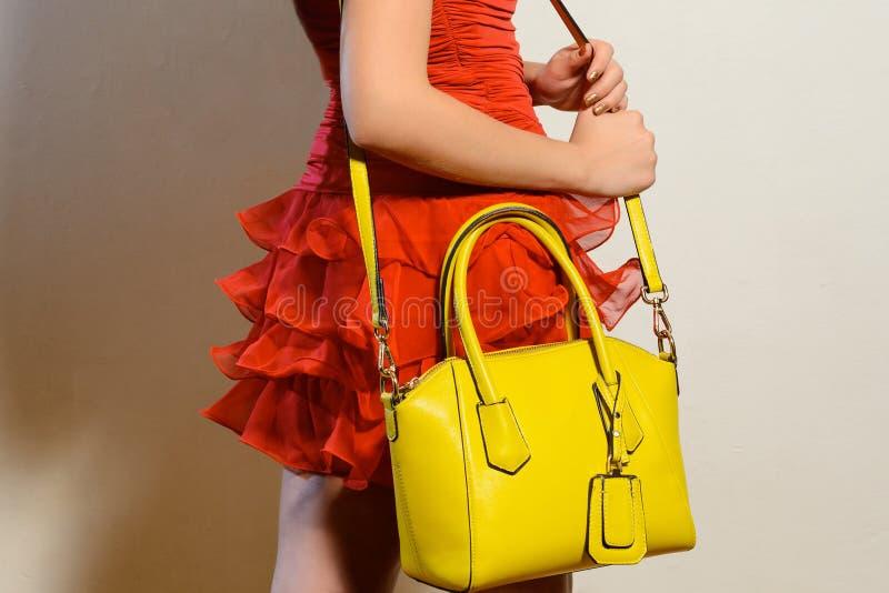 Modieuze jonge vrouw in een rode kleding met gele handtas stock afbeeldingen
