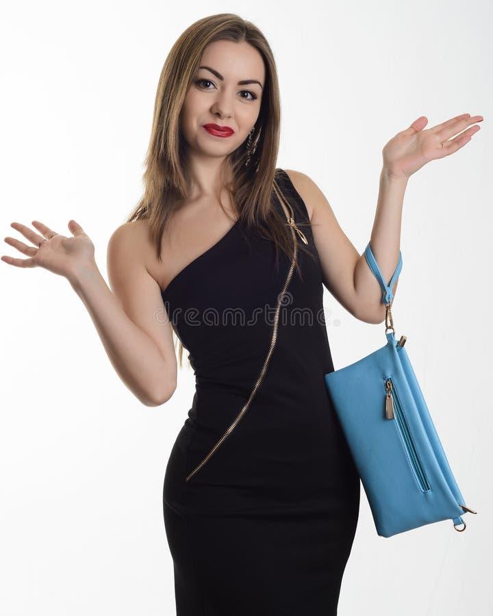 Modieuze jonge vrouw in een zwarte avondjurk met een blauwe koppelings bevindende handen uitgestrekt aan de kanten van verrassing royalty-vrije stock afbeelding