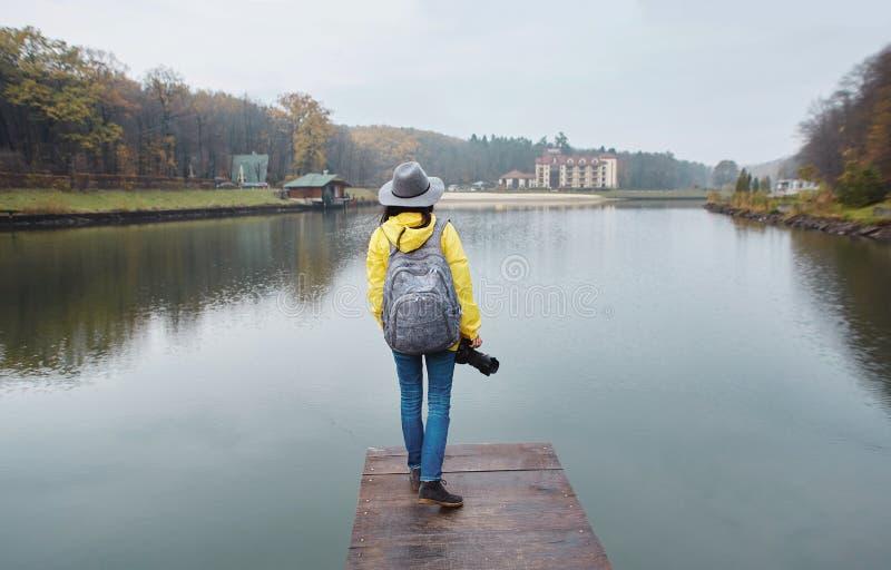 Modieuze jonge vrouw in gele waterdichte regenjas en hoed, die op de houten pijler door het meer in het park bij de herfst lopen stock afbeelding