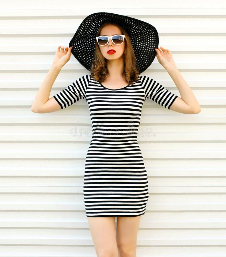 Modieuze jonge vrouw in gestreepte kleding, de hoed van het de zomerstro het stellen op witte muur royalty-vrije stock afbeeldingen