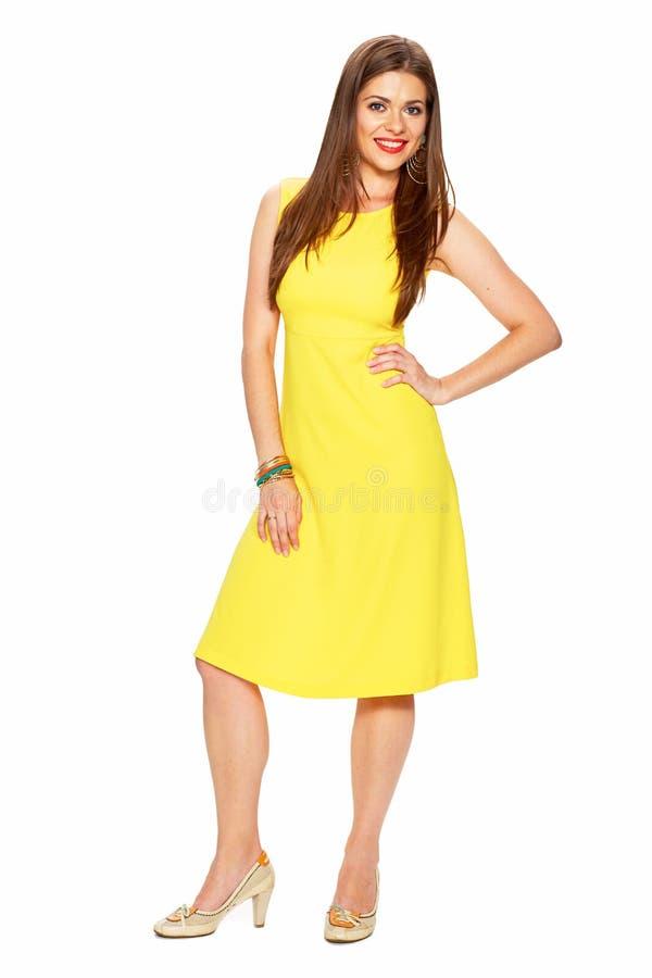 Modieuze jonge vrouw in het gele kleding stellen op witte backgro stock afbeelding