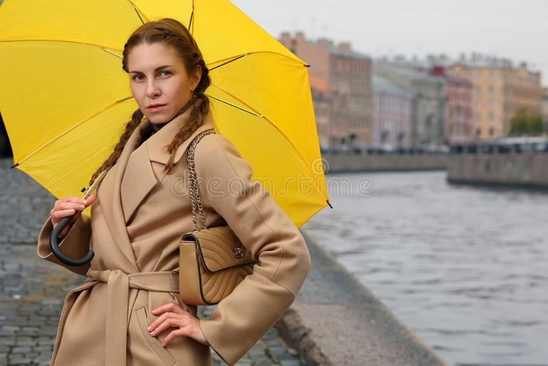 Modieuze jonge vrouw met gele paraplu stock afbeelding