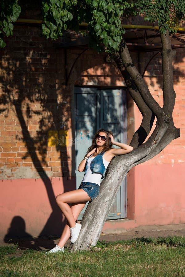 Modieuze jonge vrouw in sexy denimborrels en zonnebril sexy royalty-vrije stock foto's
