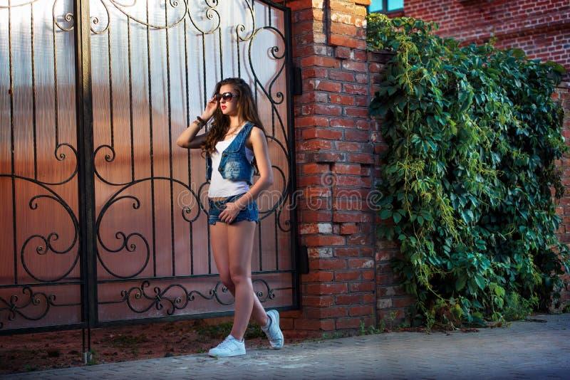 Modieuze jonge vrouw in sexy denimborrels en zonnebril sexy donkerbruin meisje met sportief lichaam die jeansborrels dragen stock foto's