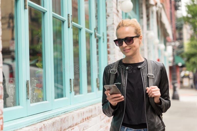 Modieuze Jonge Vrouw in Zwart Leerjasje en Bezig met haar Mobiele Telefoon terwijl het Lopen van een Stadsstraat stock fotografie