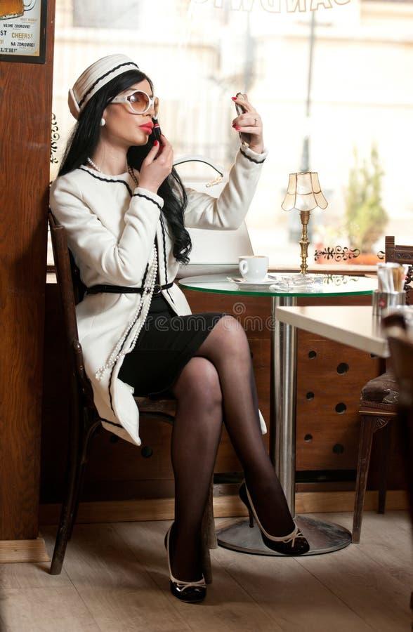 Modieuze jonge vrouw in zwart-witte uitrusting die lippenstift op haar lippen zetten en koffie in restaurant drinken royalty-vrije stock afbeelding