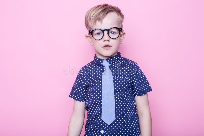 Modieuze jongen in overhemd en glazen met grote glimlach school peuter Manier Studioportret over roze achtergrond stock afbeelding