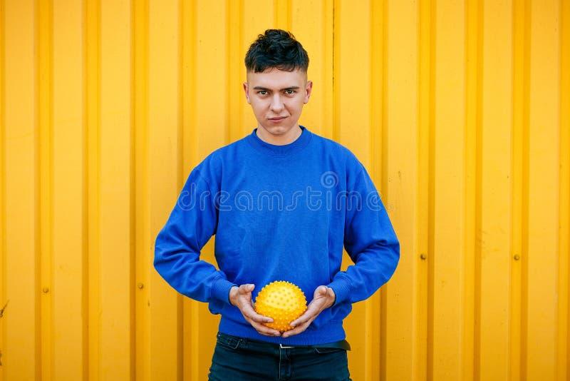 Modieuze kerel in blauwe sweater met gele bal stock afbeelding