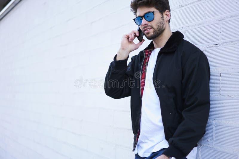 Modieuze kerel in lichte jeans, een witte T-shirt en een donker jasje royalty-vrije stock fotografie