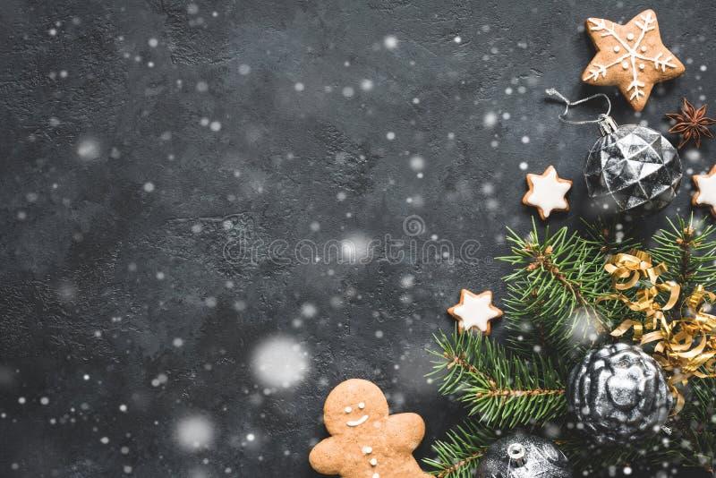 Modieuze Kerstmisachtergrond met dalende sneeuw, uitstekend speelgoed, spar en koekjes op zwarte steen stock foto's