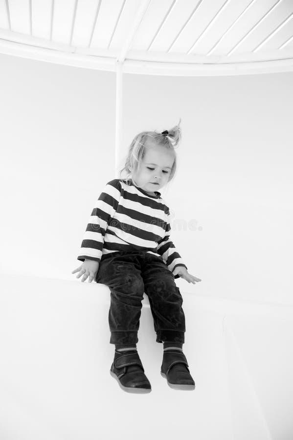 Modieuze kleine babyjongen op boot in marien overhemd, broek stock foto