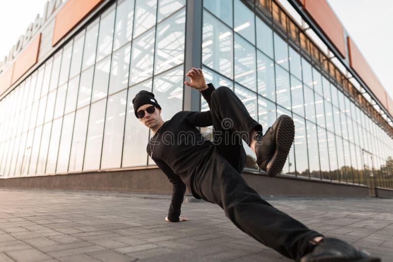 Modieuze knappe jonge hipstermens in modieuze donkere zonnebril in in zwarte kleren het dansen onderbrekingsdans royalty-vrije stock afbeeldingen