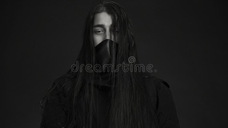 Modieuze knappe jonge mens Kaukasisch man portret mens in zwarte kleren met donker lang haar royalty-vrije stock afbeeldingen