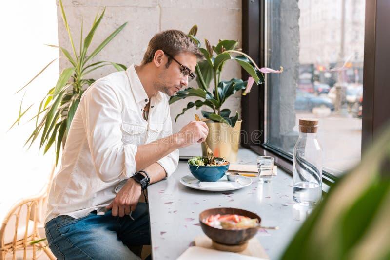 Modieuze knappe mens die wit overhemd dragen die lunch in veganistkoffie eten royalty-vrije stock fotografie