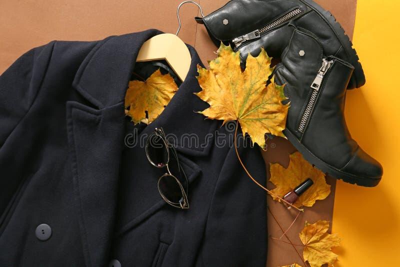 Modieuze laag met laarzen en de herfstbladeren op kleurenachtergrond, hoogste mening stock foto