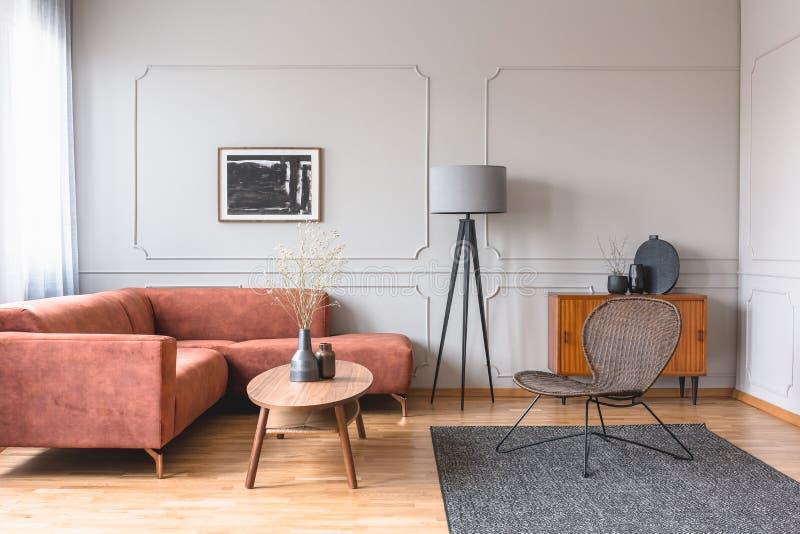 Modieuze lange grijze lamp in elegant woonkamerbinnenland met comfortabele bruine hoekbank stock foto