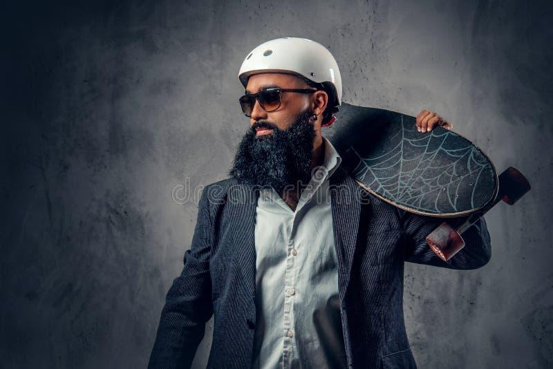 Modieuze mannelijk gekleed in een grijs kostuum houdt lange raad royalty-vrije stock foto