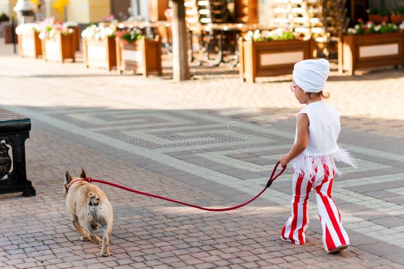 Modieuze meisjegangen met een hond langs een stadsstraat stock foto's