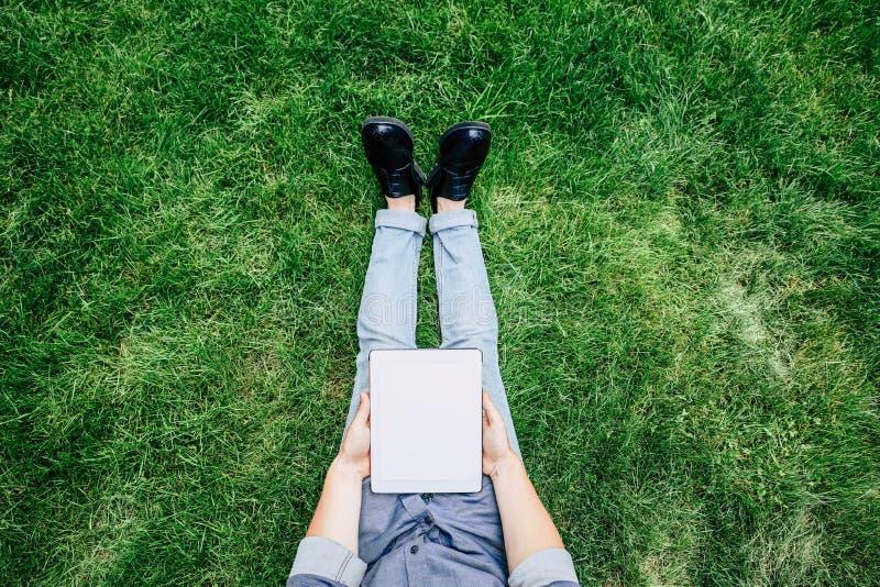 Modieuze mens die digitale tablet met het lege scherm gebruiken terwijl het zitten op groen gras royalty-vrije stock foto