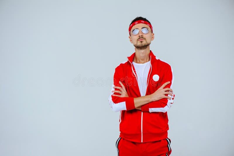 Modieuze mens die een rood sportenkostuum en glazen dragen trots en succesvol royalty-vrije stock foto's