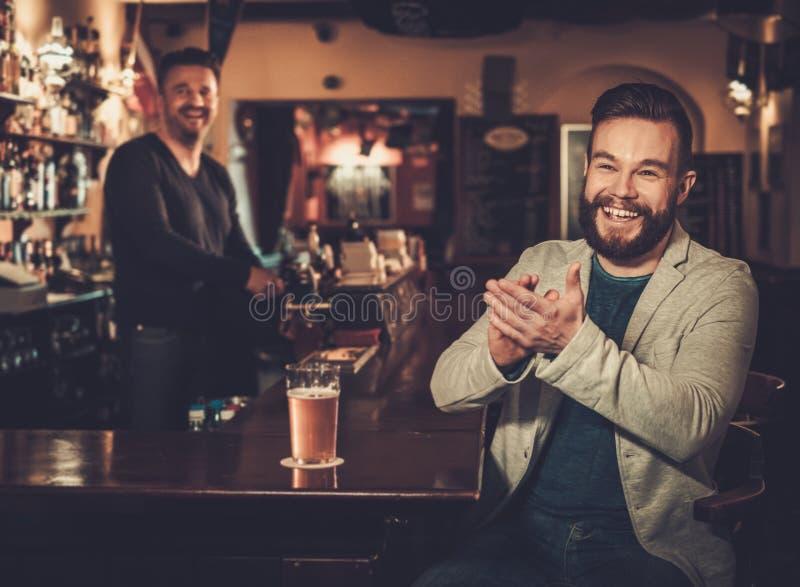 Modieuze mens die pret hebben die op een voetbalspel op TV letten en ontwerpbier drinken bij barteller in bar stock foto's