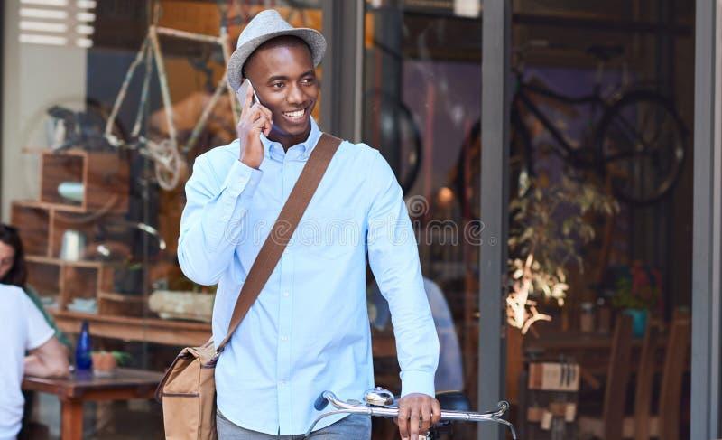 Modieuze mens die zich met zijn fiets bevinden die op een cellphone spreken royalty-vrije stock foto