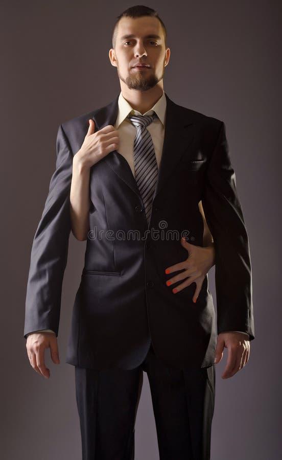 Modieuze mens in een kostuum en band op grijze achtergrond royalty-vrije stock foto