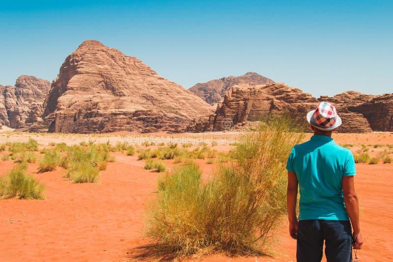 Modieuze mens in hoed dragen en T-shirt die verbazend landschap bekijken die van het leven genieten Reiziger, vrijheidsreis, luxe stock afbeeldingen