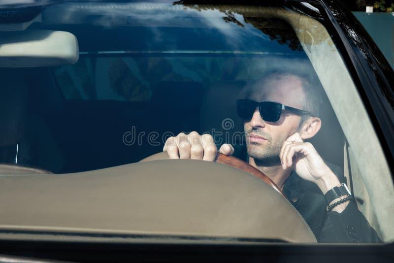 Modieuze mens in kostuum in zwarte auto Bedrijfsmens in glazensittin stock foto's