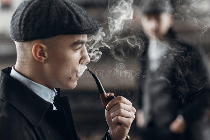 Modieuze mens in retro uitrusting, rokende houten pijp sherlock holme royalty-vrije stock afbeeldingen