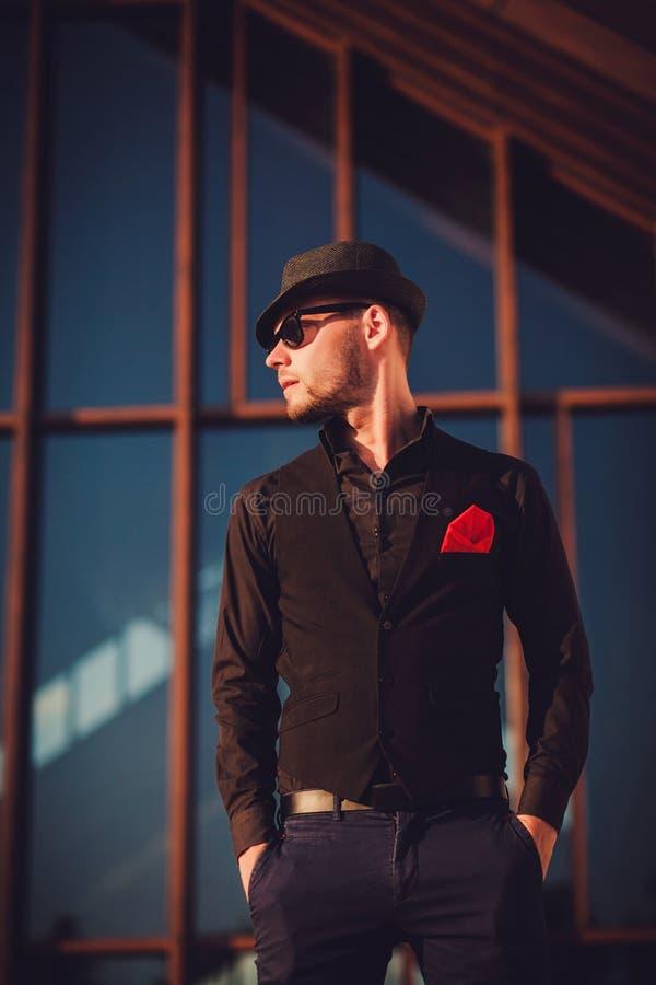 Modieuze mens in zonnebril die dichtbij de moderne bouw stellen royalty-vrije stock fotografie
