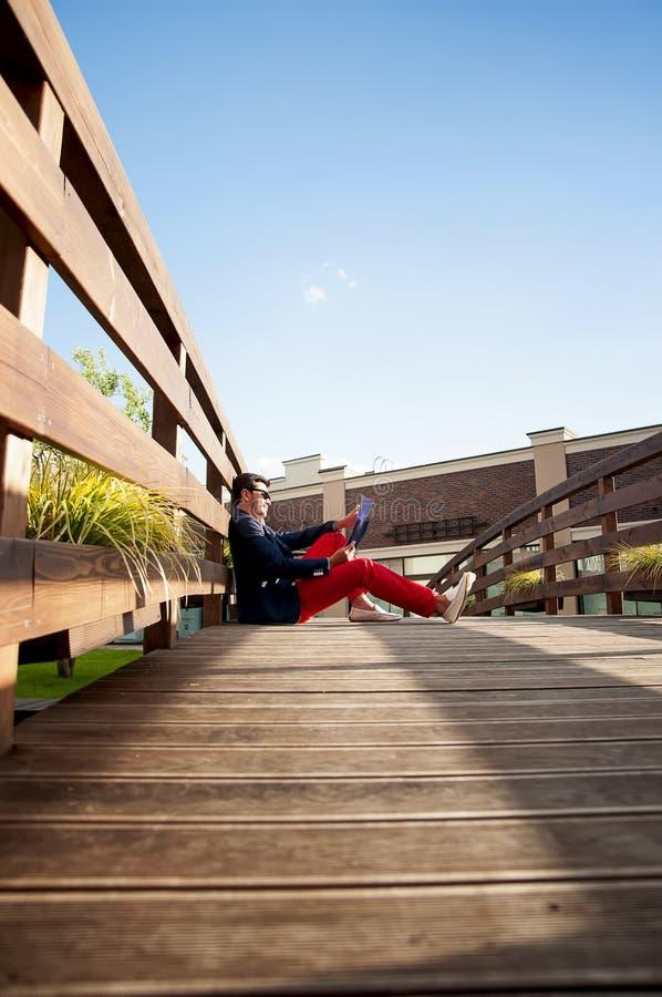 Modieuze mensenzitting op houten brug stock afbeeldingen