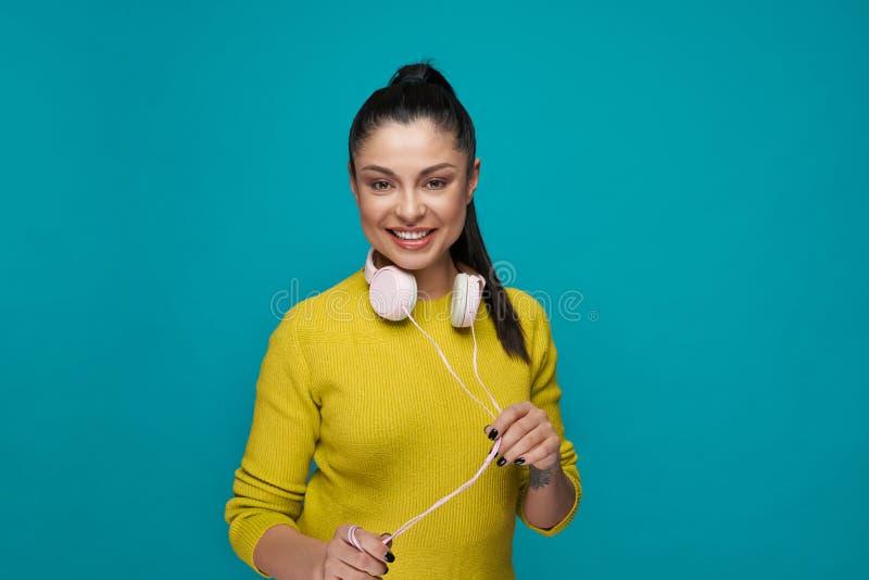 Modieuze model met hoofdtelefoons die, het glimlachen stellen stock afbeelding