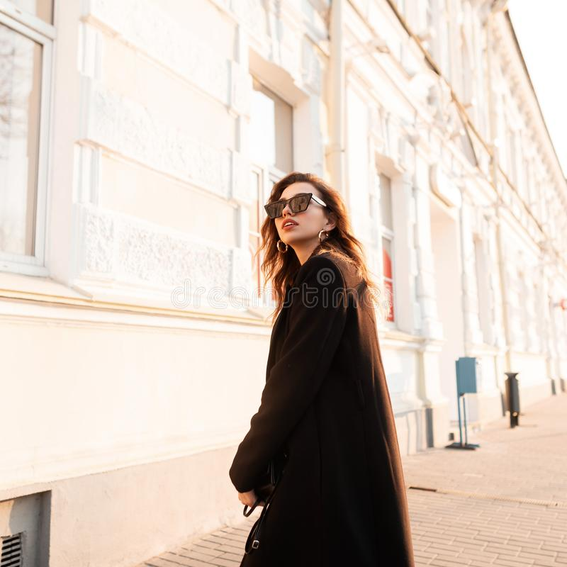 Modieuze moderne jonge donkerbruine hipstervrouw in zwarte elegante lange laag in modieuze zonnebril die dichtbij een wit gebouw  stock foto