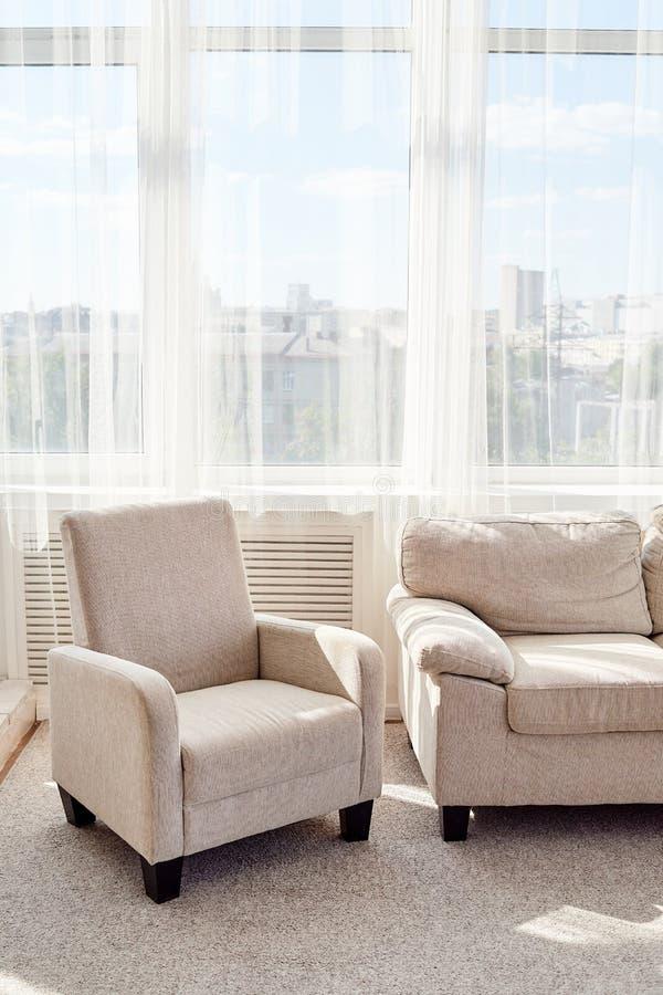 Modieuze moderne woonkamer met comfortabele beige bank en leunstoel en groot venster, exemplaarruimte Het binnenland van de woonk stock fotografie