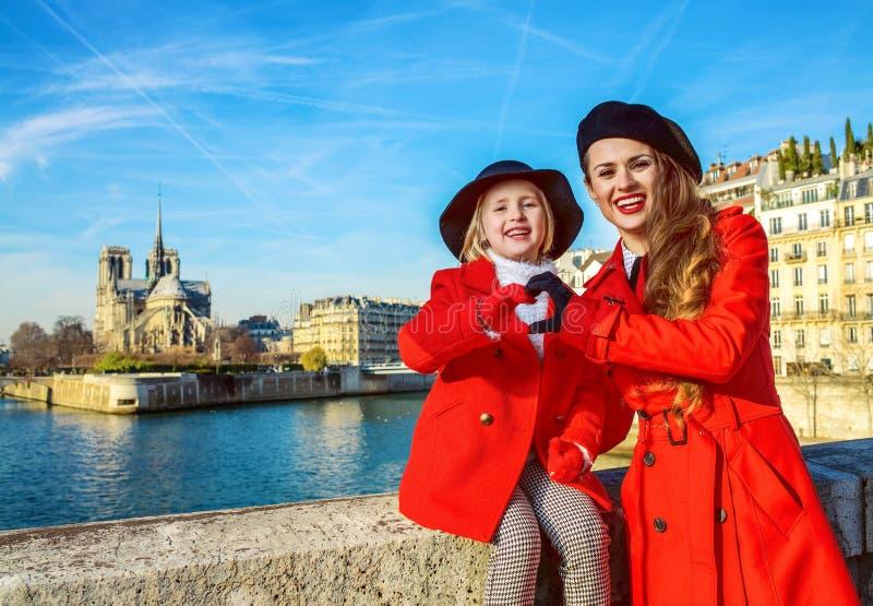 Modieuze moeder en dochter in Parijs die hart gevormde handen tonen stock foto